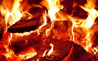 Carbon, as carbon dioxide, is released from flaming logs to enter the atmosphere.