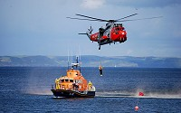 Coast guard training with a helicopter and a cutter.